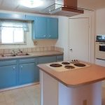 Small kitchen with blue cabinets and stove top on detached island